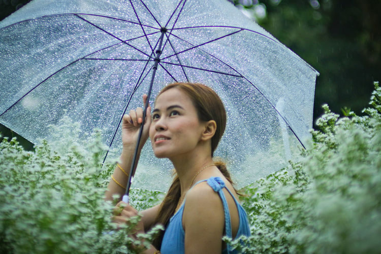 Portrait of woman standing on wet rainy day
