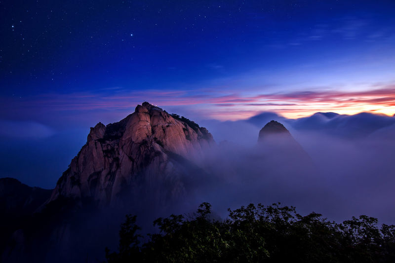 Bukhansan mountains is covered by morning fog and sunrise in Seoul,Korea Astronomy Beauty In Nature Galaxy Landscape Milky Way Moon Mountain Nature Night No People Outdoors Physical Geography Rock - Object Scenics Sky Star - Space Star Trail Tranquil Scene Tranquility