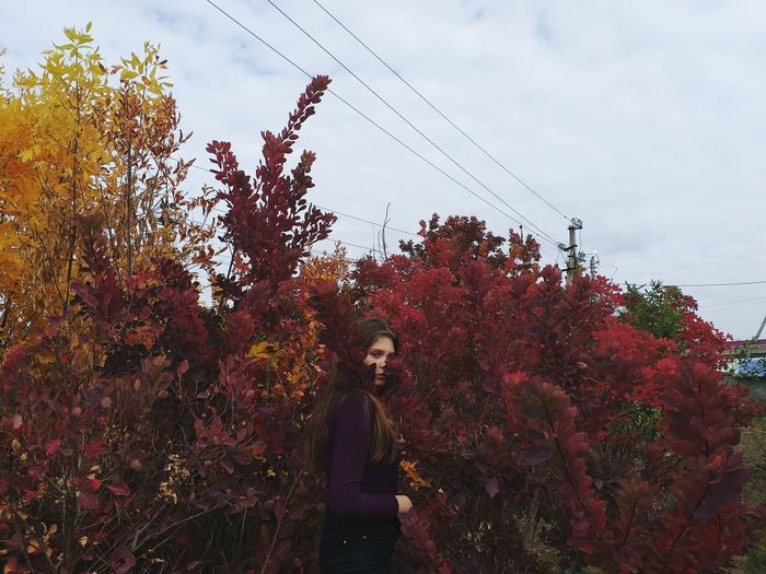 Portrait of young woman standing by plants against sky