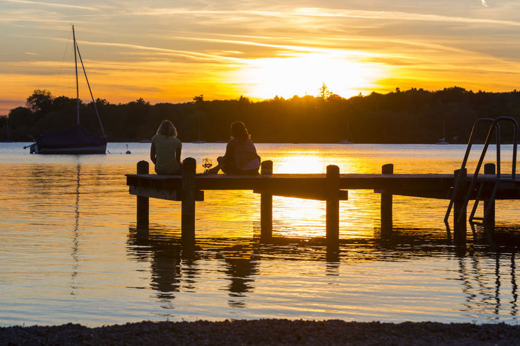 Rear view of female friends resting on jetty over lake during sunset