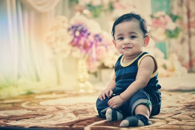 Portrait of cute boy sitting on carpet