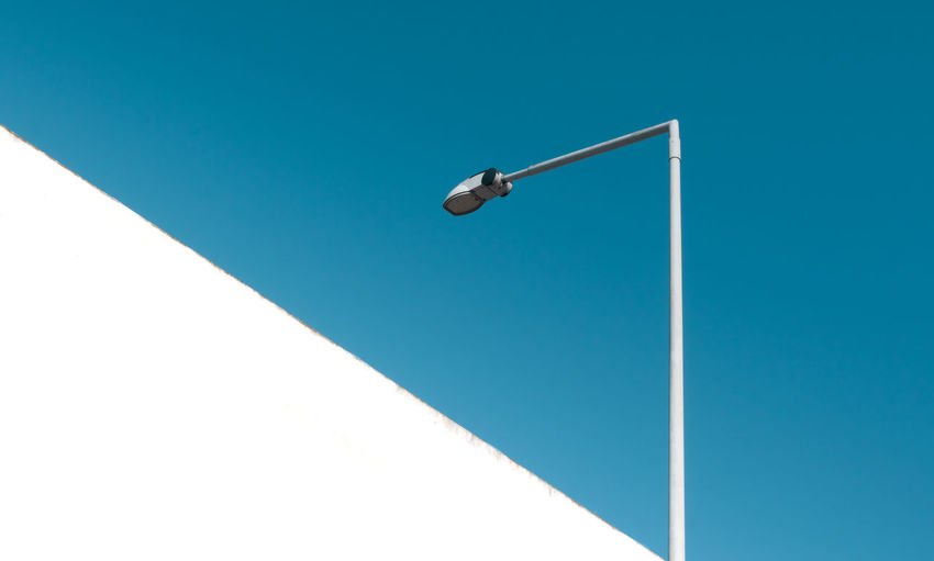 Low angle view of street light and concrete wall against blue sky