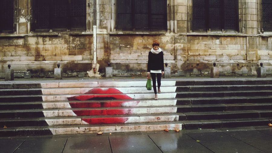Woman walking on sidewalk in city