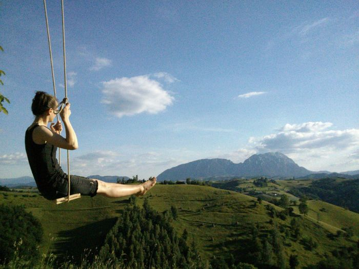 Side view of woman sitting on swing against landscape