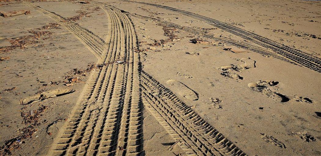 High angle view of tire tracks on sand