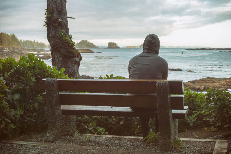 Rear View Of Man Sitting On Bench By Sea Against Sky