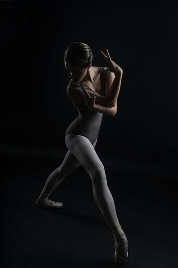 Full length of woman dancing against black background
