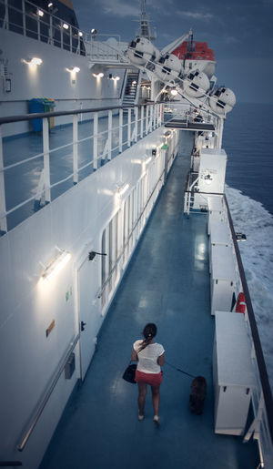 High angle view of woman with dog walking on boat deck in sea