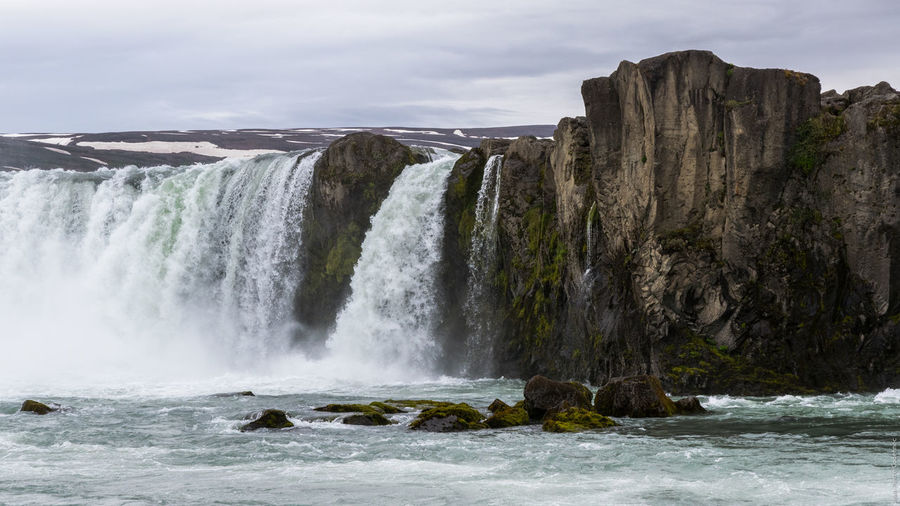 Low angle view of godafoss against cloudy sky