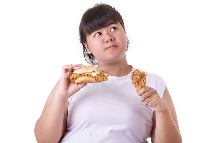 Portrait of woman holding ice cream against white background