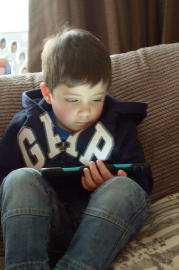 A young boy playing on a tablet computer. Boy Gadget Indoors  Ipad Lifestyles Person Playing Relaxation Sat Down Seated Settee Sitting Sitting Sitting Pretty Sofa Tablet Technology Young Young Adult