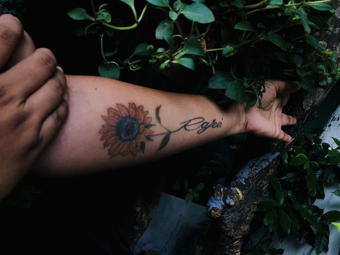 Close-up of tattoo on hand by plants