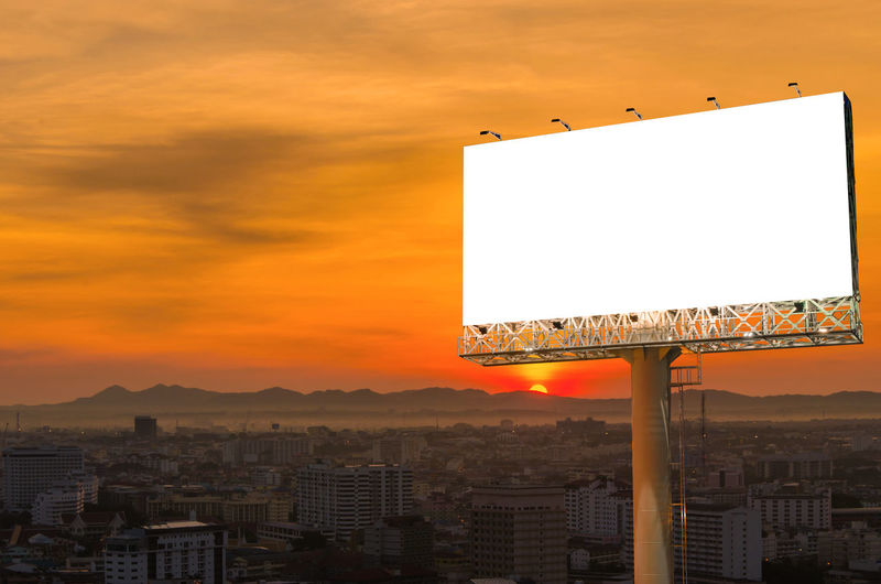 Sunset Architecture Built Structure Building Exterior Sky Orange Color Billboard Advertisement Communication City No People Nature Cityscape Outdoors Copy Space Sign Blank Cloud - Sky Building Residential District Message