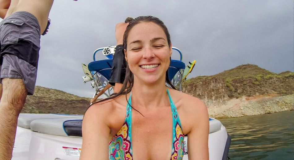 Cheerful smiling woman wearing bikini while sitting in nautical vessel at sea
