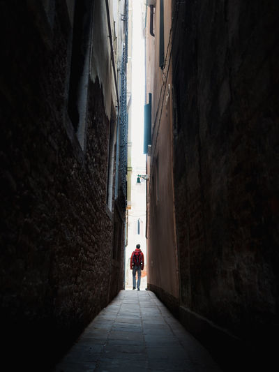 Rear view of people walking on narrow alley amidst buildings