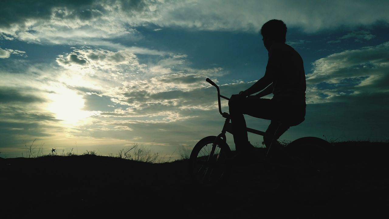 bicycle, silhouette, cycling, transportation, riding, sky, leisure activity, one person, real people, sunset, mode of transport, land vehicle, lifestyles, nature, men, cloud - sky, full length, mountain bike, bmx cycling, landscape, outdoors, healthy lifestyle, beauty in nature, scenics, cycling helmet, day, people