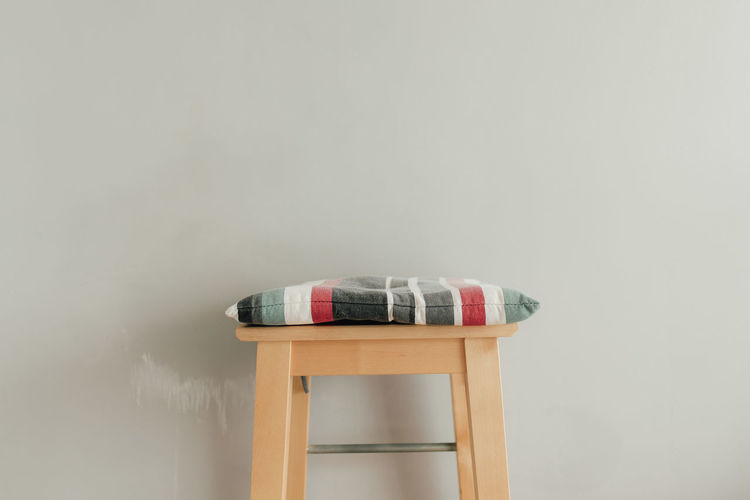 Close-up of empty seat with cushion against wall