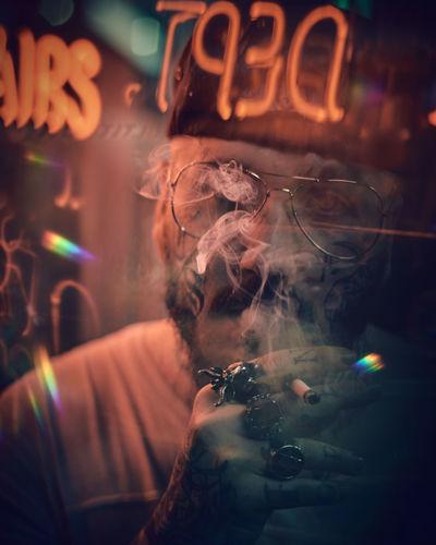 Close-up of man smoking at night