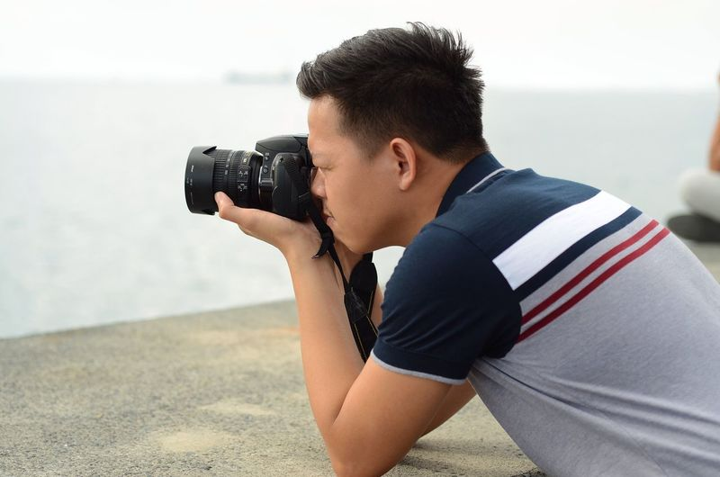 Capturing Photographer One Person Camera - Photographic Equipment Photography Themes Real People Leisure Activity Photographing Lifestyles Photographic Equipment Technology Land Young Men Day Beach Casual Clothing Holding Activity Water Photographer Young Adult Digital Camera