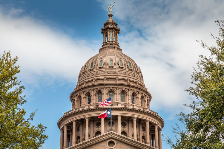 Texas State Capitol Building in Austin, with the flags of Texas and the USA Texas Capitol Austin Flag Patriotism State Building Capital Sky Day Downtown Dome Government Travel Blue Architecture City USA Landmark Monument Congress Old Historic Federal Tourism Stone Cloud Statue America Law Politics United Legislature  TX Political Symbol Spring Space Green Building Exterior Built Structure Low Angle View Travel Destinations Nature No People Arch The Past History Architectural Column Spire