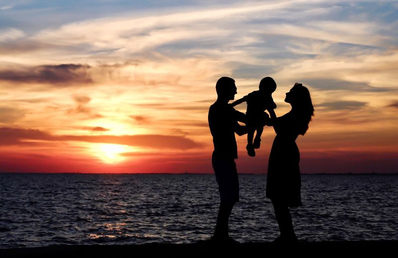 Silhouette couple against sea during sunset