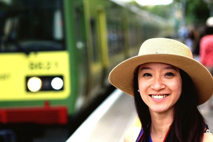 Portrait of smiling woman wearing hat at railroad station