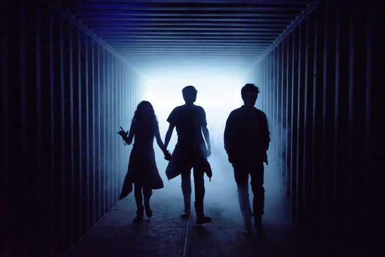 Rear view of silhouette people walking in corridor