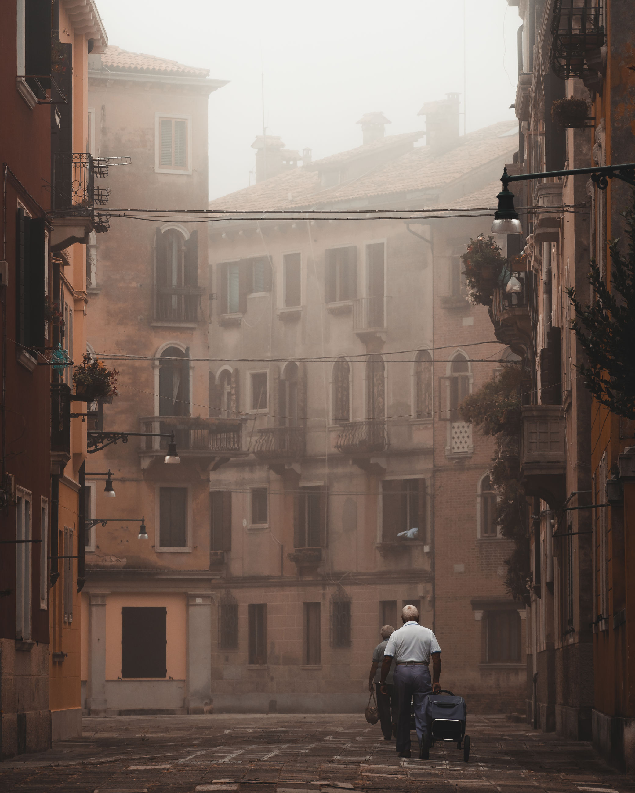building exterior, city, architecture, built structure, street, real people, building, men, residential district, one person, rear view, transportation, fog, day, lifestyles, outdoors, city life, incidental people, mode of transportation