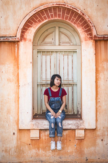 Full length of young woman sitting on window sill in old building