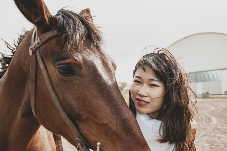 Close-up portrait of young woman with horse on land against sky
