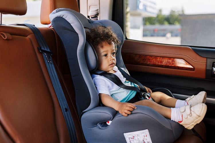 Baby boy sitting on seat in car