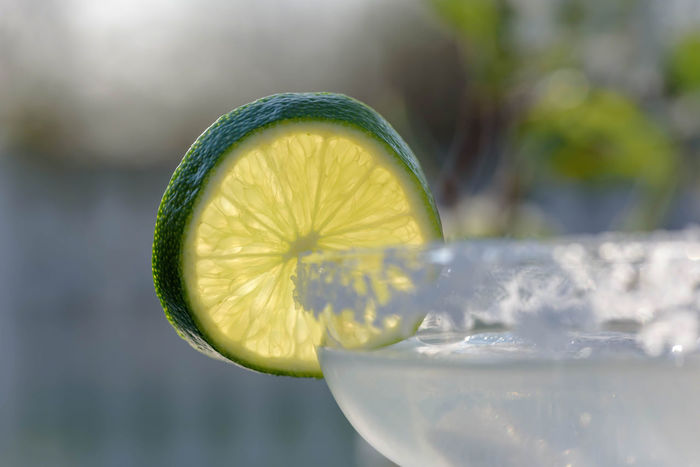 Closeup of margarita glass with lime garnish in the sunlight Celebration Cinco De Mayo Cocktail Copy Space Drinks Frozen Margarita Margarita Sunlight Alcohol Alcoholic Drink Celebrate Citrus Fruit Closeup Drink Drinking Glass Food And Drink Fruit Glass Lime Outdoors Party Refreshment SLICE Summer