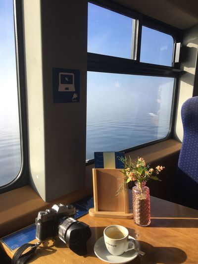 Mit dem Katamaran über den Bodensee bei Sonne über das Wasser mit Kaffee und Kamera Bodensee Katamaran Ship Camera Window No People Nature Day Glass - Material Indoors  Table Sunlight Sky Food And Drink Transparent Water Transportation Vehicle Interior Drink