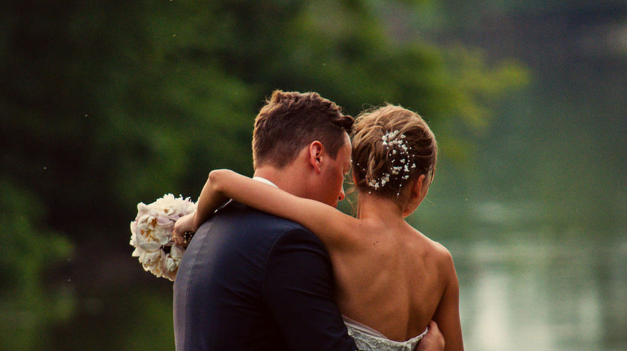 Bride and bridegroom standing by lake