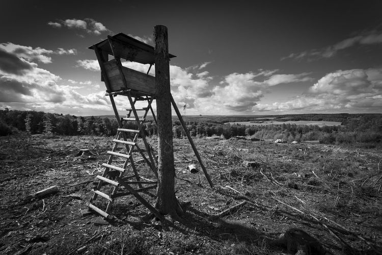 Old chair on field against sky