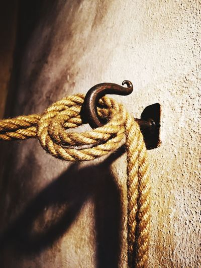 Close-up low angle view of rope tied on hook in wall