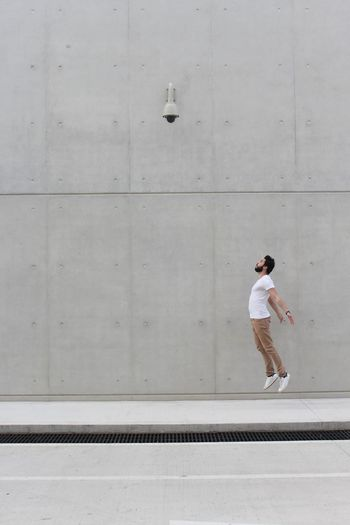Full length of young man walking on concrete wall