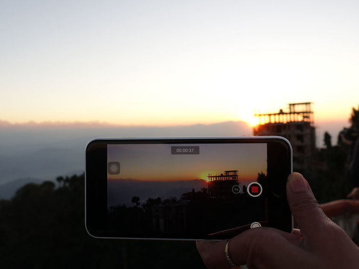 Man photographing smart phone against sky during sunset