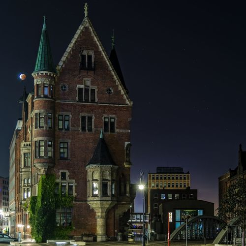 Low angle view of building at speicherstadt against sky during lunar eclipse
