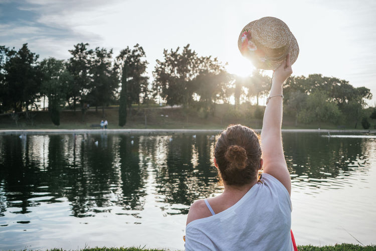 Caucasian woman from behind putting a hat to the sun in a park