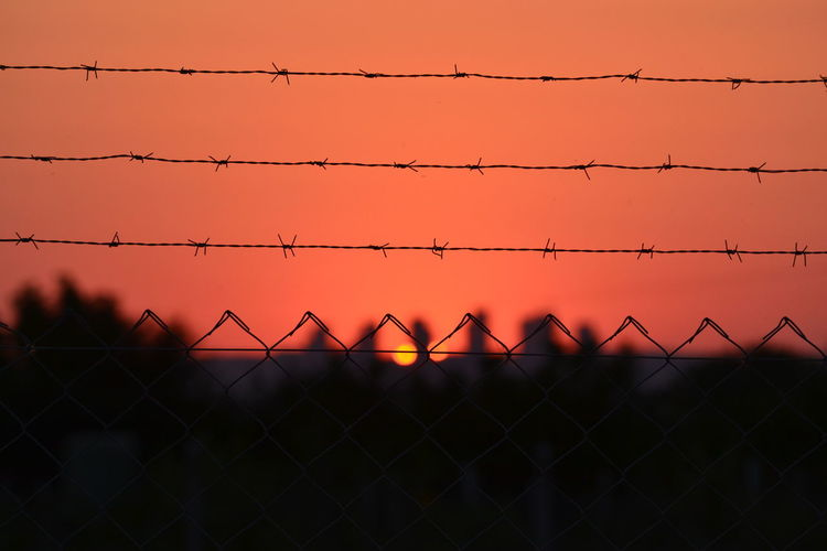 Silhouette chainlink fence against orange sky during sunset