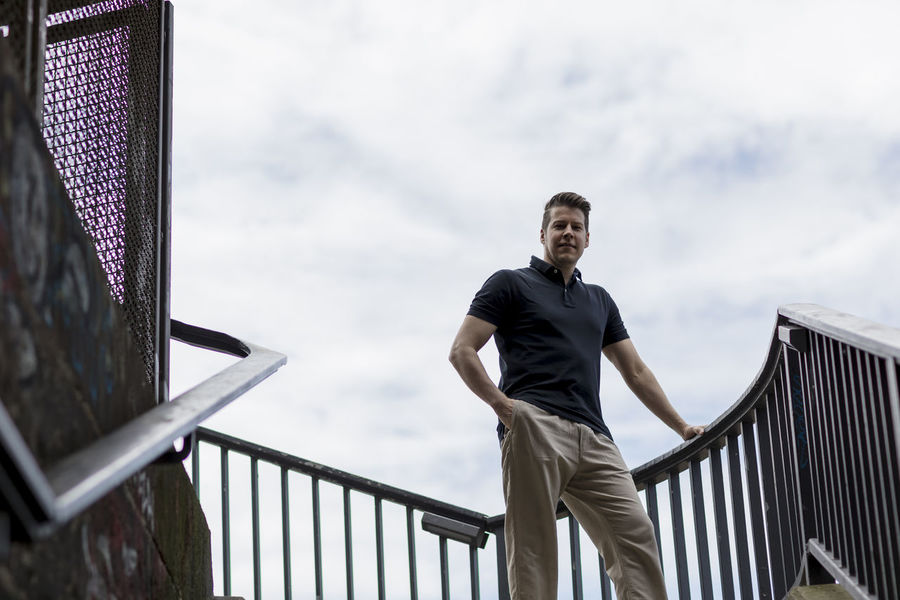 Handsome man dressed casually standing in an outdoor stairwell with one hand in his pocket. Adult Balustrade Cloudy Khaki Pants Long Shot Looking At Camera Man Stairs Standing Casual Clothing Caucasian Day Golf Shirt Good Looking Hand In Pocket Handrail  Handsome Low Angle Outside Sky Staircase Stairwell Summer Urban