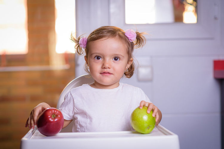 Cute baby girl with fruits on high chair at home