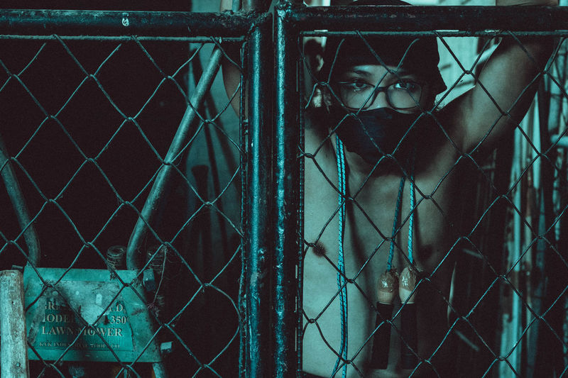 Portrait of man wearing mask seen through chainlink fence