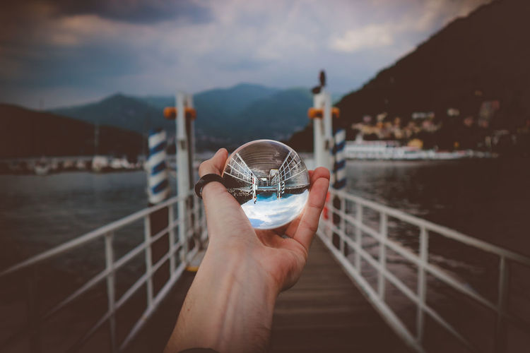 Cropped hand holding crystal ball against lake