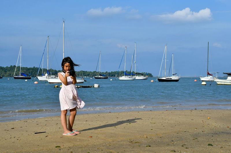 Full length of girl photographing on beach against sky