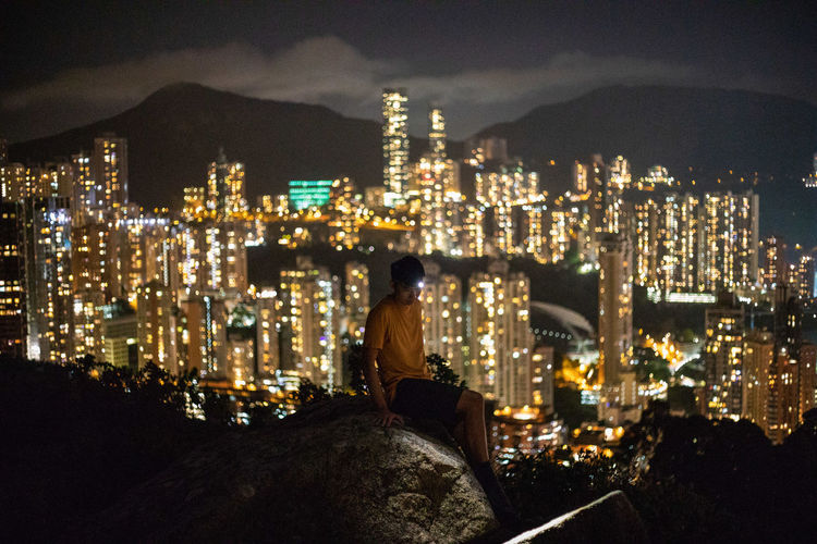 Rear view of woman sitting against illuminated buildings in city at night