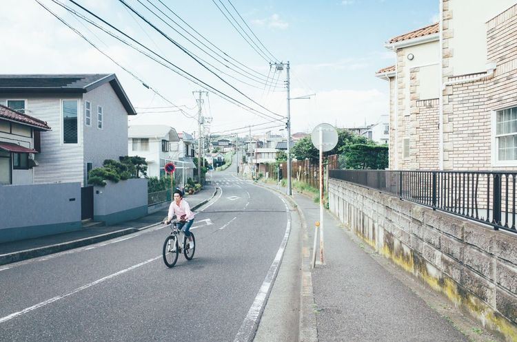 Building Exterior Built Structure Transportation Architecture Bicycle Mode Of Transport Power Line  City Cable Cycling City Life Road Day Outdoors Fuel And Power Generation One Person Riding One Man Only Electricity Pylon Sky