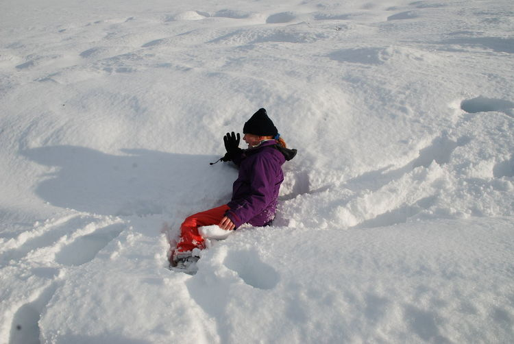 High angle view of teenage girl sitting on snow covered field