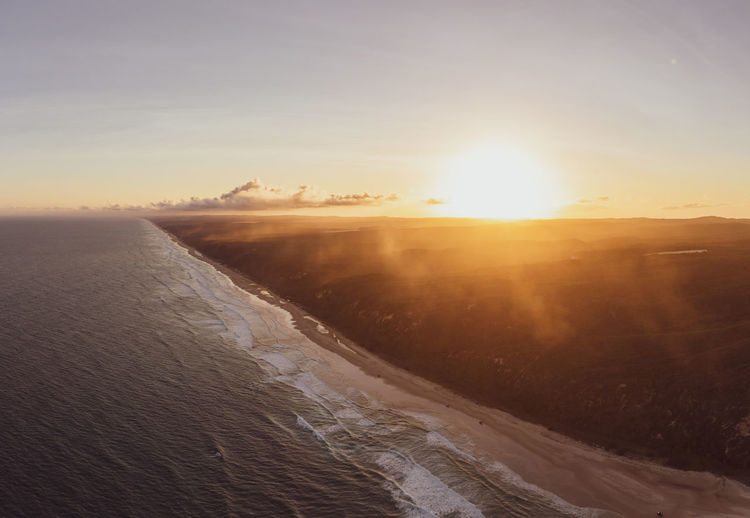 Aerial of sea against sky during sunset